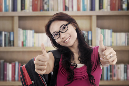 Portrait of asian college student showing thumbs-up. shot in the library