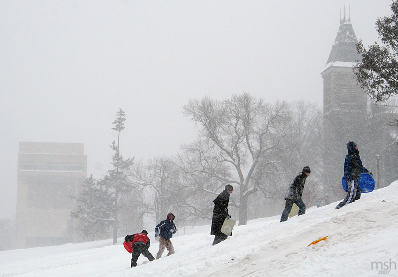 Sledders head back up libe slope after runs on their objects of choice.